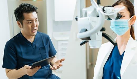 カウンセリングをする三好歯科 自由が丘の院長とマイクロスコープを使用して根管治療をする副院長